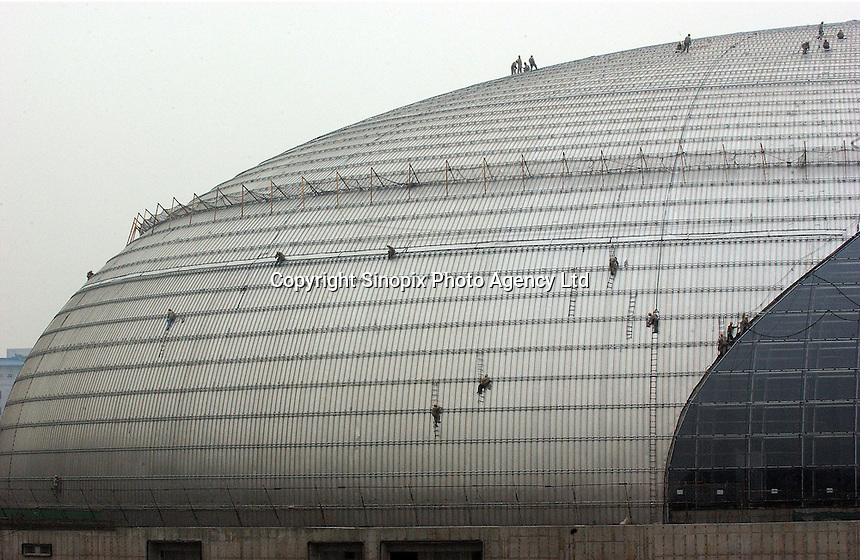 Workers secure the roof of the National Grand Theatre designed by French architect Paul Andreu, beside the Great Hall of the People in Beijing, China. The theatre, or the 'duck egg', as some residents dubbed it, is due to open diagonally opposite from the Forbidden City late this year..05-NOV-04