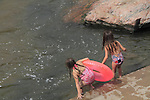 Two girls playing with an inner tube in a river, Denver, Colorado, USA.