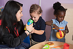 Education Preschool First days of school phase-in mother offering her child a toy as another child plays nearby toddler-2s program