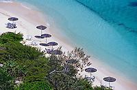 Sun umbrellas dotted along the white sand beach on Amedee Island, New Caledonia.