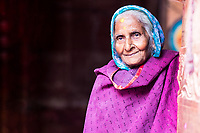 Portrait of a smiling old woman with colorful clothes, during Holi in Sri Radha Vallabh Lal temple, in Vrindavan, near Mathura Uttar Pradesh, India
