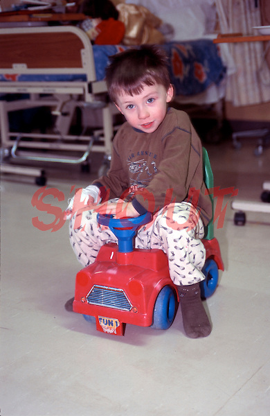 Child playing with toys on the pediatric ward of a hospital. The child is recovering from pneumonia. He has a cannular inserted into his right hand. This image may only be used to portray the subject in a positive manner..©shoutpictures.com..john@shoutpictures.com