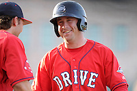 Designated hitter Tim Roberson (25) of the Greenville Drive smiles as he reaches first base in a game against the Asheville Tourists on Tuesday, July 1, 2014, at Fluor Field at the West End in Greenville, South Carolina. Asheville won, 5-2. (Tom Priddy/Four Seam Images)
