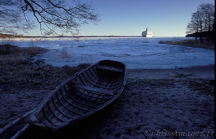 A beached dory witnesses the passing of Silja Europa on a cold winter's day in the Finnish Archipelago.
