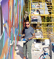 Marc Hayot/Siloam Sunday Artist Yatika Fields poses for a picture as he is painting the mural at Memorial Park