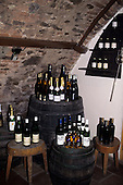 Bratislava, Slovakia: bottles of wine displayed on barrels in the cellar of a Slovak vineyard.