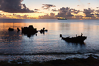The wreck of the ship 'Van Camp' lies off of the coast of the island of Fongafale in the Funafuti atoll. The ship ran aground during a typhoon in the 1970's. The last remnants of the ship's shell are slowly dissapearing to the ocean, as modern vessels (in background) continue to ply the waters nearby. Tuvalu is made up of a collection of small islands and coral atolls, totalling only 27 square kilometres, scattered over 500,000 square kilometres of ocean. The highest point throughout the country is only 5 metres above sea level, resulting in special vulnerability to sea level rise. Funafuti, Tuvalu. March, 2019.