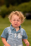 A toddler makes a face and stars to cry.