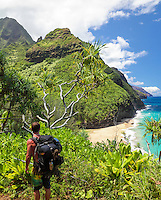 A male backpacker pauses at the view of Kanakapi'ai Beach and Na Pali coastline from the Kalalau Trail, Kaua'i.