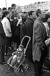 St Patricks Day Parade Hyde Park central London England 1970. Irish families at Hyde Park Corner line up and watch the parade. A child is left ignored sitting in his pram.