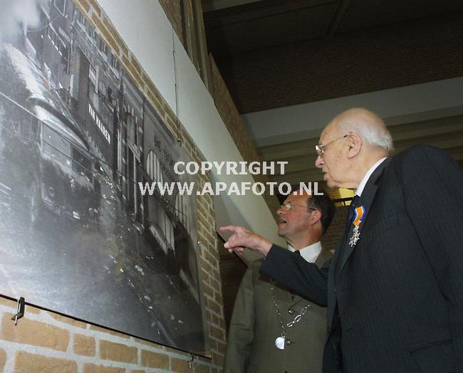 duiven 030501 de zojuist geridderde 102-jarige oud-oorlogsfotograaf P.J. de Booijs wijst burgemeester Zomerdijk van duiven  zijn fotowinkel aan op een van zijn foto's op de tentoonstelling in het duivense gemeentehuis die aan zijn werk is gewijd. met zijn 102 jaar is P.J.de Booijs de oudste onderscheide van nederland.<br />foto frans ypma APA-foto