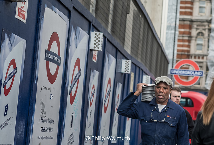Worker carrying electrical cable at the Tottenham Court Road Crossrail construction site, London.