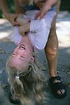 child being held upside down and tickled by her Mom while playing and having fun..Model Released