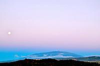 At dusk, the full moon rises over majestic Mauna Kea, as viewed from Ka'upulehu, North Kona, island of Hawai'i.