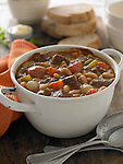 Beef stew with white beans, carrots, celery, and onion. In a rustic white pot, bread and butter in background.