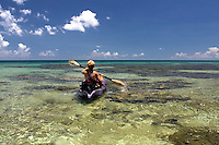 Woman (MR) with scuba equipment paddling kayak over shallow reef in Cayman Brac, Cayman Islands