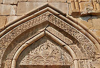 Pictures & images of the Church of the Assumption exterior bas relief Georgian stone work around the doorway,1689, Ananuri castle complex & Georgian Orthodox churches, 17th century, Georgia (country).<br /> <br /> Ananuri castle is situated next to the Military Road overlooking the Aragvi River in Georgia, about 45 miles (72 kilometres) from Tbilisi. It was the castle of the eristavis (Dukes) of Aragvi from the 13th century and was the scene of numerous battles. In 2007 Ananuri castle was enscribed on the   UNESCO World Heritage Site tentative list.<br /> <br /> The exterior of The Church of the Assumption is highly decorated with Georgian bas relief sculpture. It main portal has intricate geometric Georgian relief stone work and in its triangular tympanum are intricate stone carvings with Christ in a mondorla at its centre, and carvings of angels amongst  intricate foliage stone carvings.