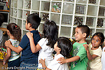 Education Preschool 3-5 year olds group of children boy and girls holding each other's shoulders in a line circle time activity I boy shorter than his peers horizontal New York City
