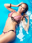 Smiling young woman wearing bikini swimsuit lying in blue water Image © MaximImages, License at https://www.maximimages.com