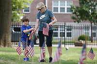 Shirley Stewart collects flags Friday, June 4, 2021, with her grandson Easton Edmonson, 6, as they volunteer with Bo's Blessing at the National Cemetery in Fayetteville. More than 8,000 flags, provided by the National Cemetery Organization, were posted on the grave sites in recognition of Memorial Day. The flags are dried, rolled up and then stored for future use. Check out nwaonline.com/210605Daily/ and nwadg.com/photos for a photo gallery.<br /> (NWA Democrat-Gazette/David Gottschalk)