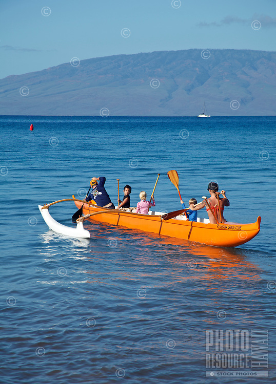 Two adults and three children in an outrigger canoe paddle towards deeper waters from Canoe Beach, West Maui.