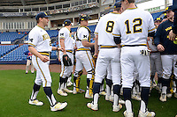 Michigan Wolverines head coach Erik Bakich (23) walks into the team meeting the first game of a doubleheader against the Siena Saints on February 27, 2015 at Tradition Field in St. Lucie, Florida.  Michigan defeated Siena 6-2.  (Mike Janes/Four Seam Images)