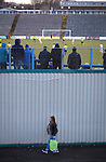 Greenock Morton 2 Stranraer 0, 21/02/2015. Cappielow Park, Greenock. A woman with a shopping bag walks outside the ground as home supporters watch action from the second-half as Greenock Morton (in hoops) take on Stranraer in a Scottish League One match at Cappielow Park, Greenock. The match was between the top two teams in Scotland's third tier, with Morton winning by two goals to nil. The attendance was 1,921, above average for Morton's games during the 2014-15 season so far. Photo by Colin McPherson.