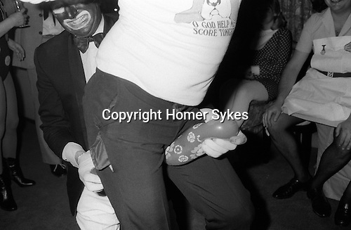 """1980's British middle class society. Christmas Fancy Dress Party London. Man in """"black face"""" dressed as a Black and White Minstrel Sexual games with man in T shirt """"O God Help Me Score Tonight""""."""