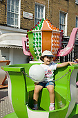 Child with a Westminster Sure Start balloon on a merry-go-round at Church Street Summer Festival 2005, Paddington, London.