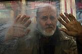 """Portraitserie von Obdachlosen in Kiew während der Corona Pandemie. Der Fotograf hat sie gebeten sich hinter dem Glas der Bahnhöfe fotografieren zu lassen. Er sagt: Ich porträtierte die Obdachlosen hinter dem Glas der Haltestellen und Unterführungen - das sind die Orte, an denen sie übernachten und leben. Das Glas ist aber auch symbolisch wie eine Wand zwischen uns und ihnen - wir sehen sie, aber wir hören sie nicht, sie sind wie Fische in Aquarien - isoliert von der Gesellschaft. Es ist nicht möglich, durch das Glas eine helfende Hand zu erreichen. Wir sympathisieren mit ihnen, wenn wir Ihnen während der Quarantäne von unseren Fenstern aus zuschauen, aber wir sind durch unsere komfortablen Wohnungen geschützt und sie blicken von unten zu unseren Fenstern hoch. / Portrait series of homeless people in Kiev during the Corona Pandemic. The photographer asked them to be photographed behind the glass of the train stations. He says: """"I portrayed the homeless behind the glass of the stations and underpasses - these are the places where they stay and live. But the glass is also symbolic like a wall between us and them - we see them but we don't hear them, they are like fish in aquariums - isolated from society. It is not possible to reach a helping hand through the glass. We sympathize with them when we watch them from our windows during quarantine, but we are protected by our comfortable apartments and they look up to our windows from below."""