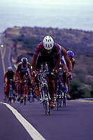 A group of muscular cyclists climb a hill during the 112 mile bicycle component of the annual Ironman triathlon on the Big Island of Hawaii.