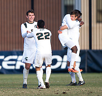 Ryan Thelen (5) of Michigan State celebrates with teammate Wesley Curtis (22) after the third round of the NCAA tournament at Shaw Field in Washington, DC. Michigan State defeated Georgetown, 1-0.