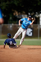 Matt McCormick receives a throw as Darell Hernaiz (8) slides in during the WWBA World Championship at the Roger Dean Complex on October 19, 2018 in Jupiter, Florida.  Matt McCormick is a catcher from Orland Park, Illinois who attends St. Laurence High School and is committed to West Virginia.  (Mike Janes/Four Seam Images)