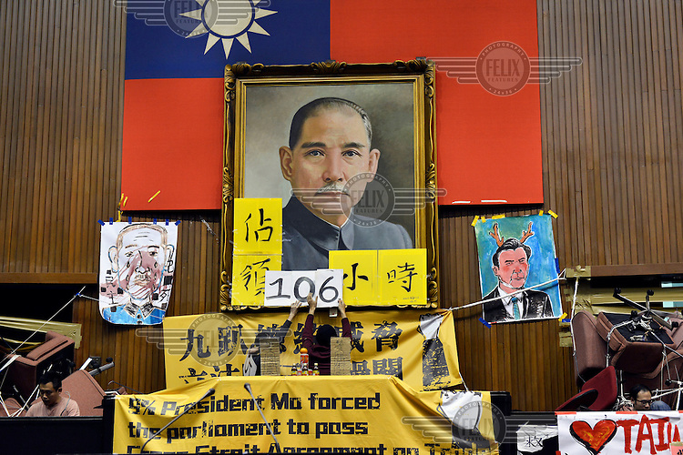 """Protestors change the marker from 105 to 106 hours that the occupation has been in progress below a giant portrait of the Republic of China's founding father, Sun Yat-Sen hanging in Taiwan's Legislative Yuan (Parliament) Building on the 4th day of its occupation by students opposed to the passing of the Cross-Straight Service and Trade Agreement between Taiwan and China. The students, and many normal Taiwanese, fear the erosion of their hard-won democracy and, eventually, independence, making them, in the words of one student protestor 'no better off than Hong Kong'. Ma ying-jeoh bears the brunt of the protestors ire; known as """"Ma 9%"""" after his latest approval rating, he is seen as kowtowing to the demands of China and selling out Taiwan."""