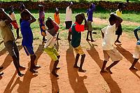 UGANDA, Karamoja, Loyoro Parish, Karamojong tribe, children dancing at church compound / Karamojong Ethnie, Kinder fuehren tadtionelle Taenze auf