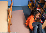 Preschool 3-4 year olds unhappy girl sitting by herself after game didn't work out