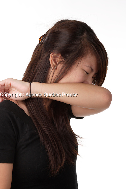 Montreal (qc) Canada -Dec 2010 - Model Released photo of a young asian adult woman covering her mouth with her arm while coughing