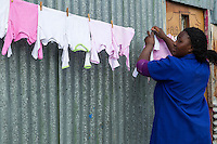 South Africa, Cape Town, Guguletu Township.  Woman Hanging her Laundry up to Dry outside the door to her house.
