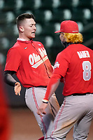 Zach Dezenzo (4) of the Ohio State Buckeyes, left, is greeted by Colton Bauer after scoring the go-ahead run in a 6-3 13-inning win over the Illinois Fighting Illini on Friday, March 5, 2021, at Fluor Field at the West End in Greenville, South Carolina. (Tom Priddy/Four Seam Images)