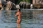 Bathing in the warm tropical waters of the Anse d'Argent beach. La Digue Island.