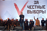 "Moscow, Russia, 24/12/2011..Russian blogger and political activist Alexei Navalny speaks to an estimated crowd of up to 100,000 gathered to protest against election fraud and Prime Minister Vladimir Putin in the largest anti-government demonstration in Russia since the collapse of the Soviet Union. The banner behind reads ""For Honest Elections""."