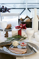 Detail of a table laid for a festive Christmas breakfast of smoked trout and homemade horseradish sauce