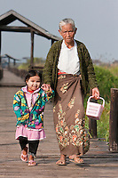 """Myanmar, Burma.  Grandmother and Granddaughter Walking near """"Floating Bridge"""", Inle Lake, Shan State.  The little girl has thanaka paste on her face, a natural cosmetic sunscreen."""