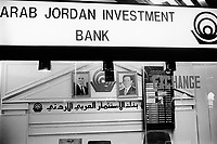 """Jordan. Amman. Arab Jordan Investment Bank. Exchange rates. Portraits of King Abdullah II and his father King Hussein, both dressed as an western business man. His Majesty King Abdullah II bin Al Hussein, is the actual King of The Hashemite Kingdom of Jordan.His Majesty King Abdullah II bin Al Hussein is the 43rd generation direct descendant of the Prophet Muhammad. He assumed his constitutional powers as Monarch of the Hashemite Kingdom of Jordan on February 7th, 1999, the day of the death of his father, the late Royal Highness King Hussein bin Talal (1935-1999), known to his  people as Al-Malik Al-Insan (""""The Humane King"""").© 2002 Didier Ruef"""