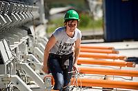 Airlight Energy, Biasca,macchina per la fabbricazione delle travi in calcestruzzo fibrato per il collettore solare. Operaia al lavoro