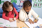 Educaton preschool 4-5 year olds two girls sitting side by side writing alphabet letters using plastic stencils bother using left hand to hold pencil horizontal