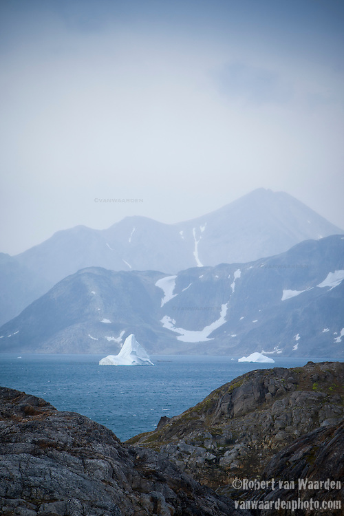 Iceberg in the mountainous landscape of Eastern Greenland.
