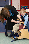 MR / Albany, NY.Langan School at Center for Disability Services .Ungraded private school which serves individuals with multiple disabilities.Teaching assistant buckles child into his Rifton chair. Boy: 9, cerebral palsy, non verbal with expressive and receptive language delays.MR: Law4; Ber8.© Ellen B. Senisi