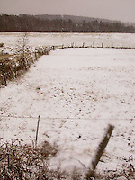 Fence bisecting snow covered field<br />