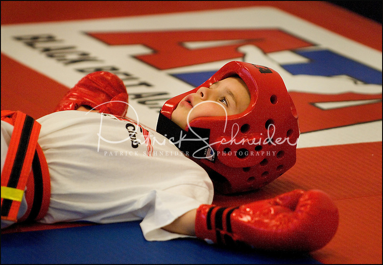 A young boy (model released) practices the art of Tae Kwan Do, a sport he was just beginning to learn, as shown by the white belt, which signifies beginner.  Photographer has many photos of children participating in Tae Kwan Do classes (at different ages and different belt/degrees of achievement).